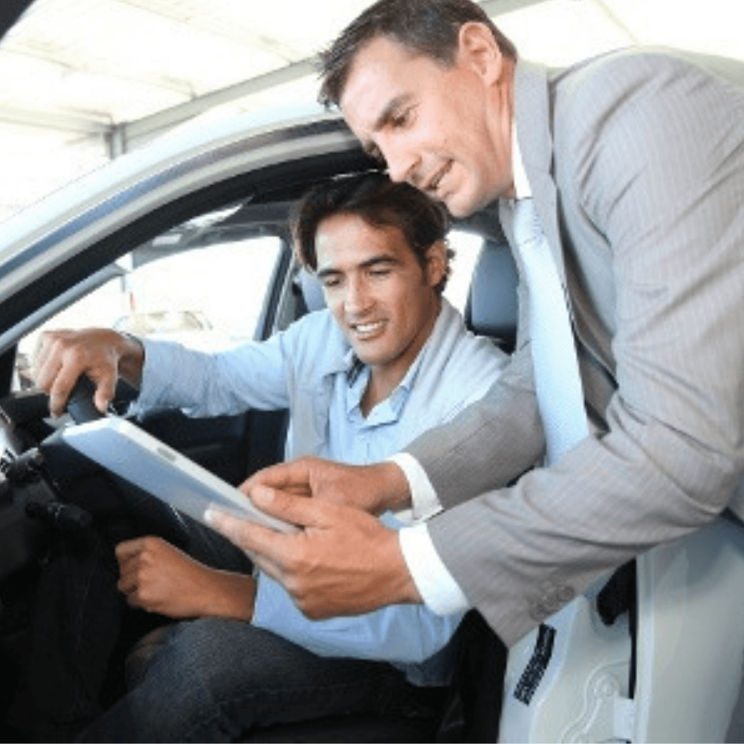car salesman with buyer in car showing contract