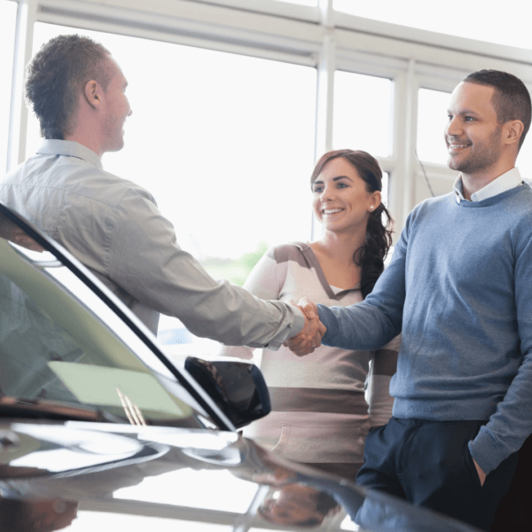 man shaking hands with car dealer